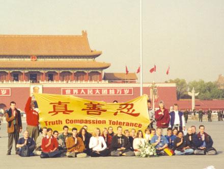 Заграничные практикующие Фалуньгун держат плакат с надписью иероглифами «истина доброта терпение». Через минуту к ним применят силу. Пекин