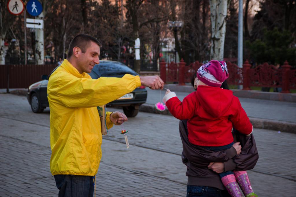 Маме с ребенком дарят бумажный лотос - символ милосердия и душевной чистоты Фалуньгун